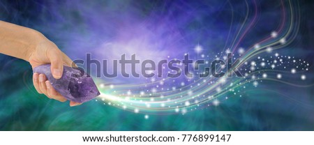 Massive Amethyst with beautiful energy - female hand holding large terminated amethyst quartz wand  shooting out sparkles across a purple and jade energy background with copy space  #776899147