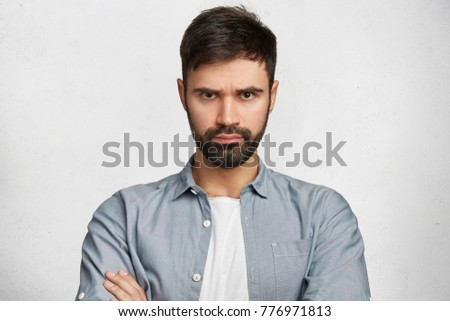 Portrait of serious displeased male stands crossed hands against white background, scowl face in dissatisfaction, has quarrel with wife. Discontent man has stubble, expresses annoyannce and negativity #776971813