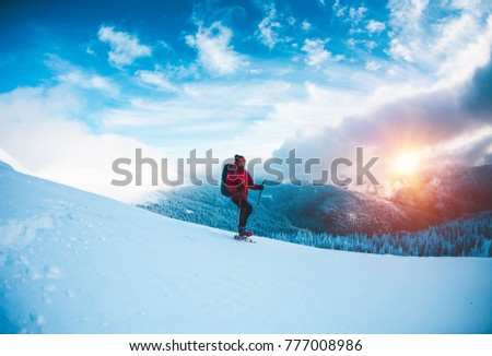 A man in snowshoes and trekking sticks in the mountains. Winter trip. Climbing of a climber against a beautiful sky with clouds. Active lifestyle. Climbing the mountain through the snow. #777008986