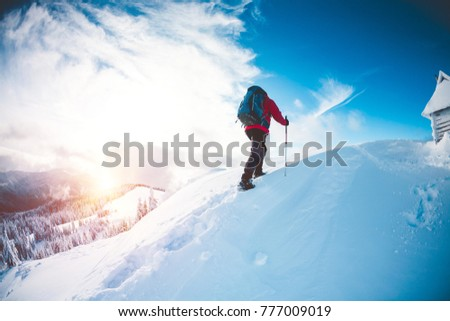 A man in snowshoes and trekking sticks in the mountains. Winter trip. Climbing climber against the background of sky with clouds. The tourist found shelter. House in the mountains. A hut in the snow. #777009019