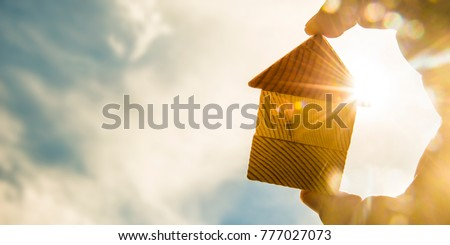 hand holds the last pieces of wooden house puzzle on blue sunny sky background. wooden home made from natural material of jigsaw. puzzle in the form of wood house. for sale or rent #777027073