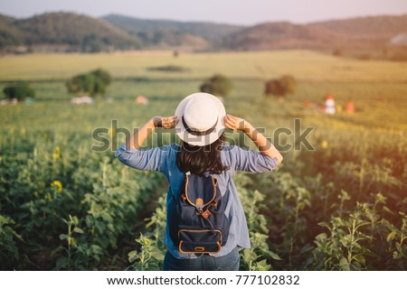 Asian woman traveler with backpack holding hat and looking at amazing mountains and forest, travel holiday relaxation concept.