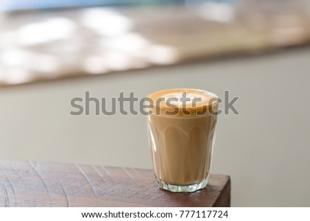 A Cup of Piccolo latte coffee with latte art on the wooden table background. #777117724