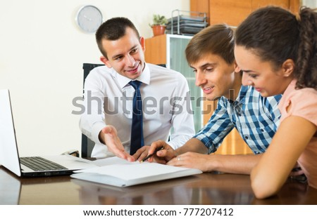Positive agent discussing with young couple details of contract in office  #777207412