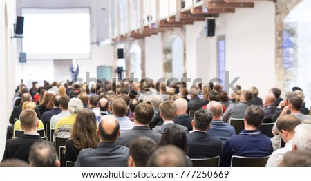 Speaker giving a talk in conference hall at business event. Audience at the conference hall. Business and Entrepreneurship concept. Focus on unrecognizable businessman in the audience. #777250669