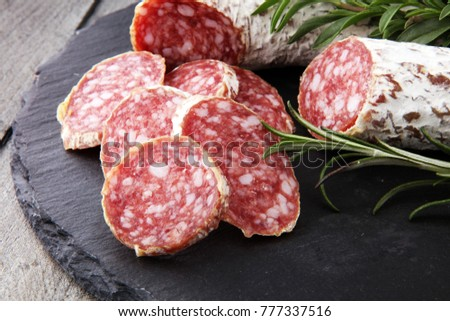 Stone cutting board with sliced salami on it #777337516