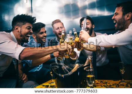 Group of young men toasting at a nightclub #777379603