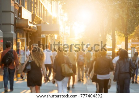 Crowd of anonymous men and women walking down an urban sidewalk with bright glowing sunlight in the background on a busy street in downtown Manhattan, New York City  Royalty-Free Stock Photo #777404392