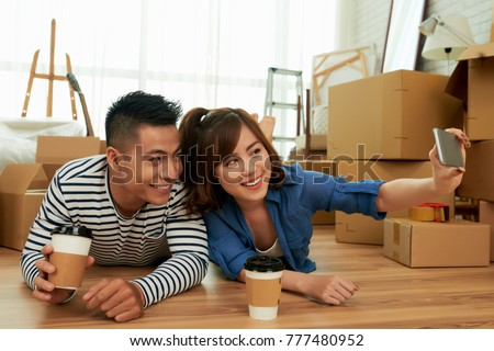 Cheerful Vietnamese couple taking selfie in their new apartment #777480952