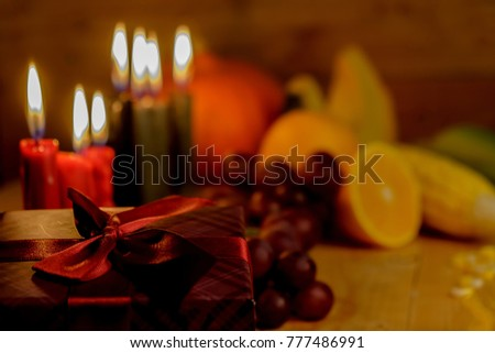Kwanzaa holiday concept with decorate seven candles red, black and green, gift box, pumpkin,corn and fruit on wooden desk and background.