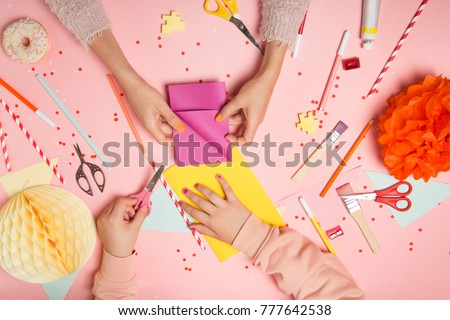 Colorful pink background with various party confetti, paper decoration, flags, stationary, DIY accessories with woman's and kid's hands making greeting card. Fat lay top view. Party arrangement #777642538