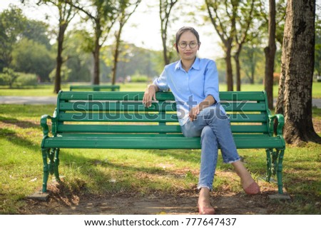 Asian woman sitting on bench in the gargen #777647437