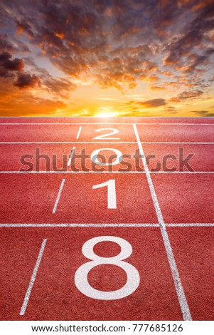 2018 Happy New Year text on athletics sport running track with sunrise sky and clouds #777685126