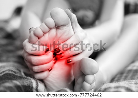 pain in the foot, girl holds her hands to her feet, foot massage, cramp, muscular spasm, red accent on foot, black and white photo, close-up #777724462
