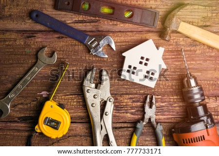 Wooden white house toy and construction tools on wooden background with copy space.Real estate concept, New house concept, Finance loan business concept, Repair maintenance concept Royalty-Free Stock Photo #777733171