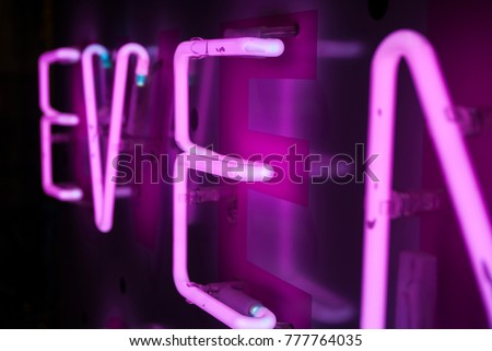 Neon sign Design element for your design, greeting card, banner.Glowing font. Close-up of a neon tube.Led wall