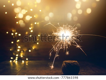 burning sparkler and christmas lights on wooden background #777861598