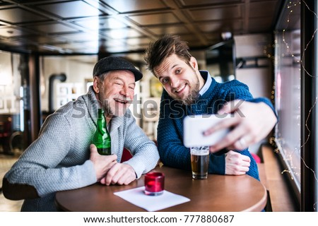 Senior father and his young son with smartphone in a pub.