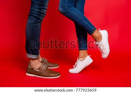 Closeup photo of woman and man legs in jeans, pants and shoes, girl with raised leg, stylish couple kissing during date, isolated over red background, he vs she Royalty-Free Stock Photo #777923659