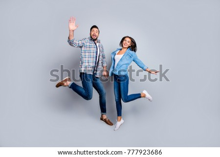 He and She full length portrait of attractive, playful, cheerful, couple in casual outfit, hold hands, jumping  over grey background, valentine day, 14 february #777923686
