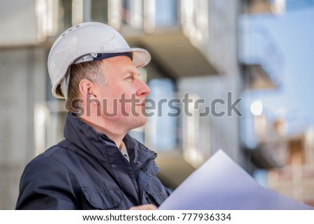 Construction manager with blueprints standing in front of construction site. #777936334