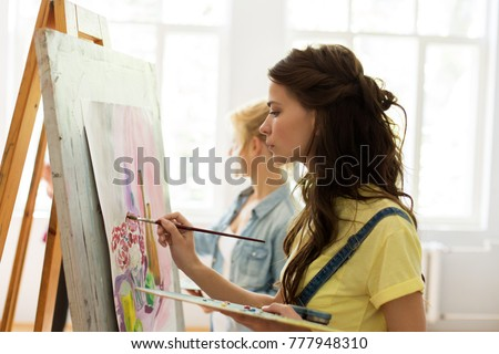 art school, creativity and people concept - woman with easel, palette and brush painting at studio #777948310