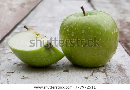 Green apple with water drops on the wooden surface #777972511