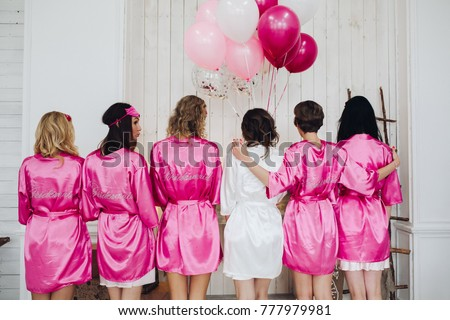 Back view of group of bridesmaids with bride-to-be in beautiful silk robes with different names on their backs. Royalty-Free Stock Photo #777979981