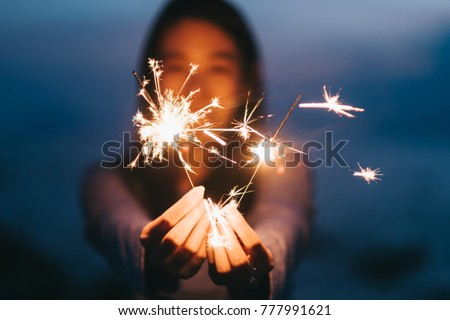 Young happy woman stands on beach with sparkler in sunset light. #777991621