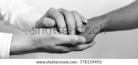 Two people holding hands for comfort. Doctor consoling relatives of patients in hospital concept. black and white. banner panoramic crop for copy space. #778159492