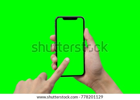 Man's hand shows mobile smartphone with green screen in vertical position isolated on green background