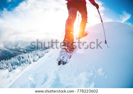 A man in snowshoes in the mountains in the winter. A climber with trekking sticks walks through the snow. Winter ascent. Beautiful sky with clouds. #778223602