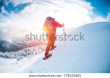 A man in snowshoes in the mountains in the winter. A climber with trekking sticks walks through the snow. Winter ascent. Beautiful sky with clouds. #778223605