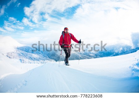 A man in snowshoes in the mountains in the winter. A climber with trekking sticks walks through the snow. Winter ascent. Beautiful sky with clouds. #778223608