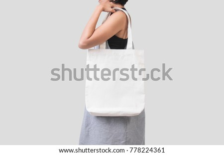 Girl is holding bag canvas fabric for mockup blank template isolated on gray background.  #778224361