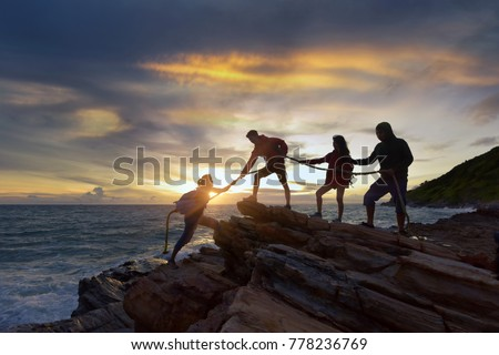 silhouette male and female hikers climbing up  mountain cliff . helps and team work concept.