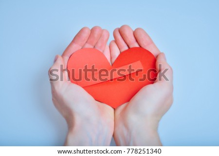 Hands with handmade red paper heart with space for writing on the blue background #778251340