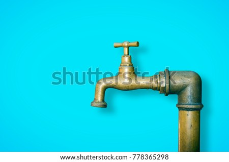 Detail of a water brass faucet isolated on solid color background - image with copy space