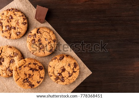 An overhead photo of chocolate chips cookies with a slice of chocolate, shot from above on a piece of baking paper, with copy space #778368451