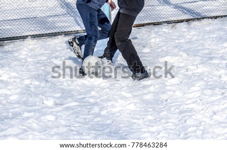 Playing football on the snow in the winter #778463284