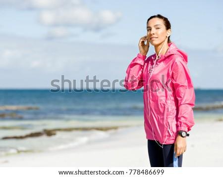 Sporty woman with earphones on the sea coast #778486699