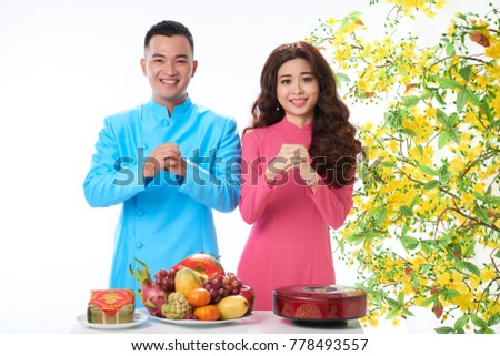 Joyful Asian couple making hand gesture to congratulate with Lunar New Year and looking at camera with toothy smiles, isolated on white background #778493557
