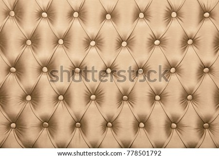 Beige capitone textile background, retro Chesterfield style checkered soft tufted fabric furniture diamond pattern decoration with buttons, close up