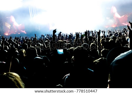 A silhouettes of concert crowd in front of bright stage lights. Dark background, smoke, concert spotlights #778510447
