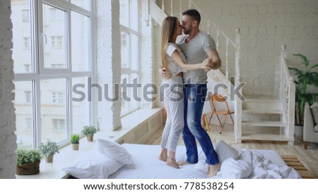 Young beautiful and loving couple dancing and kissing on bed in the morning at home #778538254