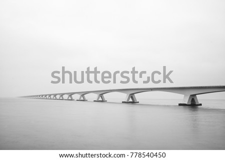 The Zeelandbrug (Zeeland Bridge) in the Dutch province of Zeeland, photographed in black & white, long exposure shot.