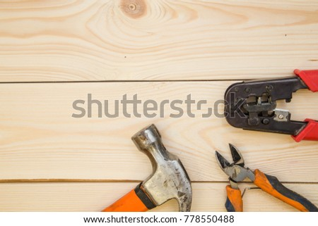 Repairing and construction concept. A set of repair tools- a hammer and pilers on a light uncolored wooden background. Top view. Space for your text or pruduct display. #778550488