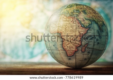 Adventure stories education background. Old globe on map background. Selective focus.