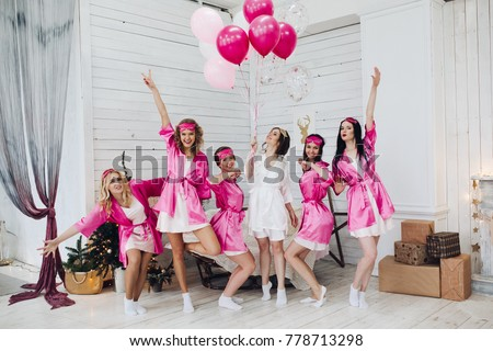 Full length portrait of happy lovely girlfriends in pink robes and sleeping masks jumping and having fun at hen party. Bride-to-be in white robe holding pink air balloons with smile standing on tiptoe #778713298