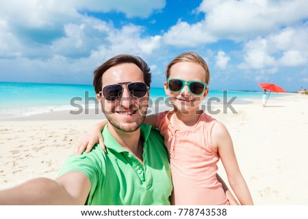 Happy family father and his adorable little daughter at beach taking selfie #778743538
